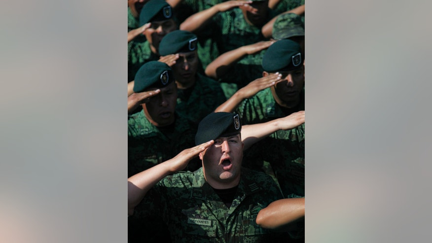 Soldiers salute Mexico's Defense Secretary Gen. Salvador Cienfuegos Zepeda at the Number 1 military camp in Mexico City, Saturday, April 16, 2016. Cienfuegos formally apologized to the country for a video-recorded incident of torture involving two soldiers and a federal police officer. He urged soldiers and citizens to come forward to report other abuses. (AP Photo/Marco Ugarte)