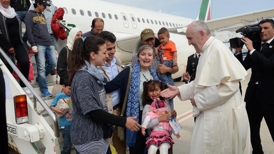 Pope Francis greets a group of Syrian refugees upon lading at Rome's Ciampino airport Saturday, April 16, 2016. Pope Francis gave Europe a provocative and concrete lesson in how to treat refugees Saturday by bringing home 12 Syrian Muslims aboard his charter plane after an emotional visit to the hard-hit Greek island of Lesbos. (Filippo Monteforte/Pool Photo via AP)