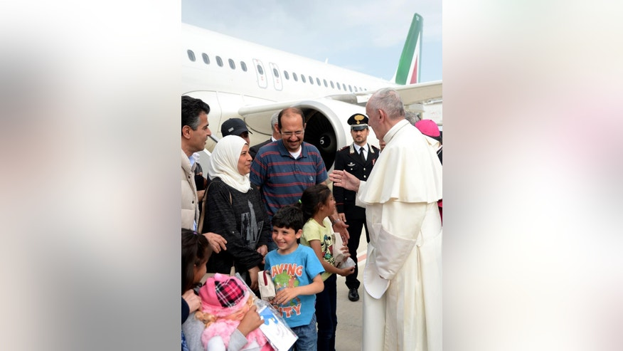Pope Francis greets a group of Syrian refugees upon landing at Rome's Ciampino airport Saturday, April 16, 2016. Pope Francis gave Europe a provocative and concrete lesson in how to treat refugees Saturday by bringing home 12 Syrian Muslims aboard his charter plane after an emotional visit to the hard-hit Greek island of Lesbos. (Filippo Monteforte/Pool Photo via AP)