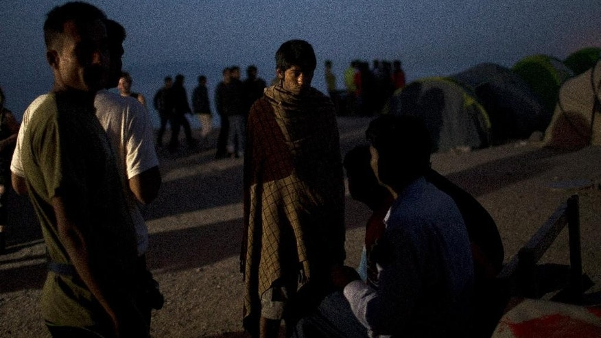 A man wrapped with a blanket chats with others in a camp set up by volunteers hosting around 250 migrants near the port of Mytilini, in the Greek island of Lesbos, on Friday, April 15, 2016. Pope Francis will visit the island Saturday joined by Ecumenical Patriarch Bartholomew and the head of the Orthodox Church of Greece, Athens Archbishop Ieronymos II, a mission human rights groups hope will highlight the plight of refugees who fled their war-ravaged homes only to be denied entry to Europe.(AP Photo/Petros Giannakouris)
