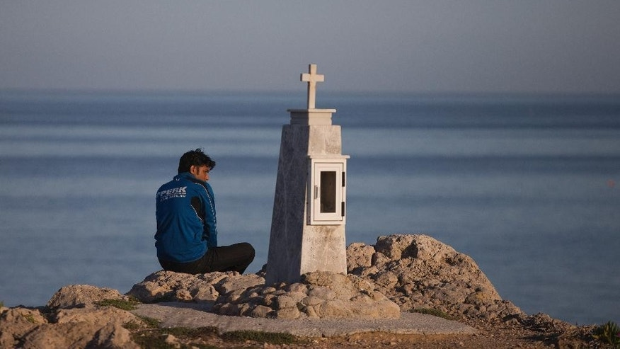 A Pakistani migrant stranded on the Greek island of Lesbos sits behind a memorial at a rocky sea side near the port of Mytilini, on Friday, April 15, 2016. Pope Francis will visit the island Saturday joined by Ecumenical Patriarch Bartholomew and the head of the Orthodox Church of Greece, Athens Archbishop Ieronymos II. During his six-hour stay, Francis will visit a camp on Lesbos where 2,300 migrants and refugees are being detained for deportation back to Turkey, under an agreement between Ankara and the European Union that human rights groups globally are railing against. (AP Photo/Petros Giannakouris)