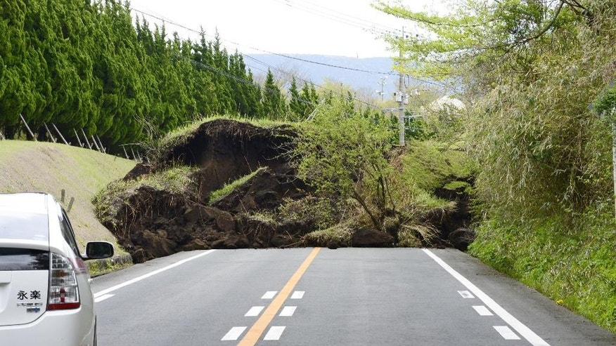 A national highway is blocked by landslide caused by an earthquake in Minamiaso, Kumamoto prefecture, southern Japan Saturday, April 16, 2016. Powerful earthquakes a day apart shook southwestern Japan, trapping many beneath flattened homes and sending thousands to seek shelter in gymnasiums and hotel lobbies. (Hiroko Harima/Kyodo News via AP) JAPAN OUT, MANDATORY CREDIT