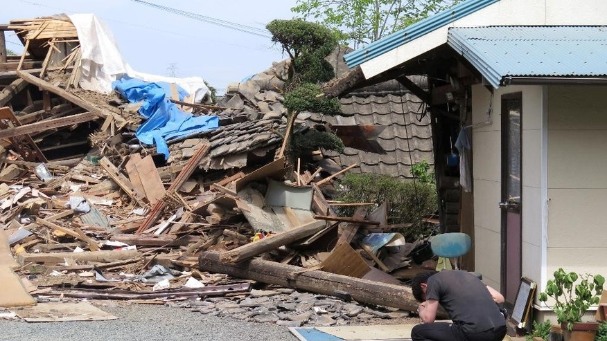 A man hunks down in front of a collapsed residence where his mother is being trapped after an earthquake in Mashiki, Kumamoto prefecture, southern Japan, Saturday, April 16, 2016. Powerful earthquakes a day apart shook southern Japan, trapping many beneath flattened homes and sending thousands to seek shelter in gymnasiums and hotel lobbies. (Kyodo News via AP) JAPAN OUT, MANDATORY CREDIT