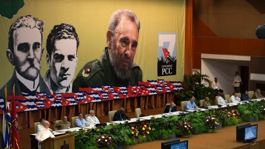 Cuba's President Raul Castro, sitting center, attends the opening of the 7th Cuban Communist Party Congress in Havana, Cuba, Saturday, April 16, 2016. Behind are images of men considered to be the party's founders, from left, Carlos Balino, Julio Antonio Mella and Fidel Castro. Raul Castro delivered a grim report on the state of the country, saying they failed to implement most of the hundreds of changes the ruling party launched five years ago to stimulate the economy. (Ismael Francisco/Cubadebate via AP)