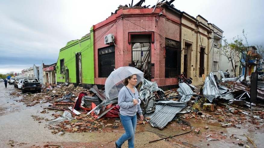 A woman walks past the rubble after a tornado swept through Dolores, Uruguay, Saturday, April 16, 2016. The powerful tornado swept over the small city on Friday, ripping up houses, hurling cars into the air and killing and seriously injuring several people, authorities said. (AP Photo/Matilde Campodonico)