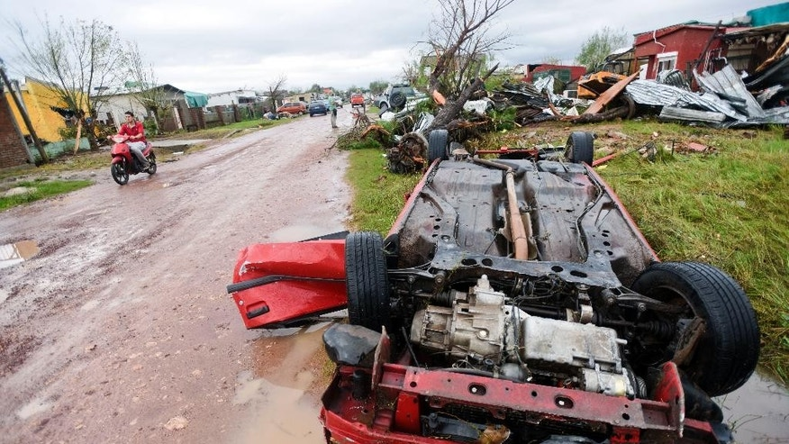 A car lays flipped over on the side of the road after a tornado swept through Dolores, Uruguay, Saturday, April 16, 2016. The powerful tornado swept over the small city on Friday, ripping up houses, hurling cars into the air and killing and seriously injuring several people, authorities said. (AP Photo/Matilde Campodonico)