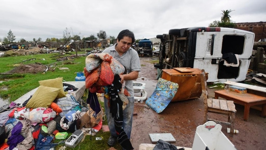 A resident cries as he picks up his belongings after a tornado swept through Dolores, Uruguay, Saturday, April 16, 2016. The powerful tornado swept over the small city on Friday, ripping up houses, hurling cars into the air and killing and seriously injuring several people, authorities said. (AP Photo/Matilde Campodonico)
