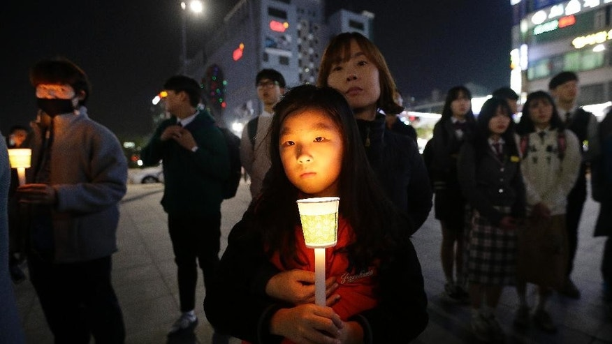 A mother and her daughter hold a candle to pay their respects to the victims of the sunken ferry Sewol during a ceremony on the eve of the second anniversary of the ferry sinking in Ansan, South Korea, Friday, April 15, 2016. Two year ago, as South Korea writhed in grief and fury after more than 300 people, most of them school kids, drowned in a ferry sinking, it seemed things would never be the same.(AP Photo/Ahn Young-joon)
