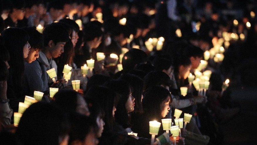High school students hold candles to pay their respects to the victims of the sunken ferry Sewol during a ceremony on the eve of the second anniversary of the ferry sinking in Ansan, South Korea, Friday, April 15, 2016. Two year ago, as South Korea writhed in grief and fury after more than 300 people, most of them school kids, drowned in a ferry sinking, it seemed things would never be the same.(AP Photo/Ahn Young-joon)