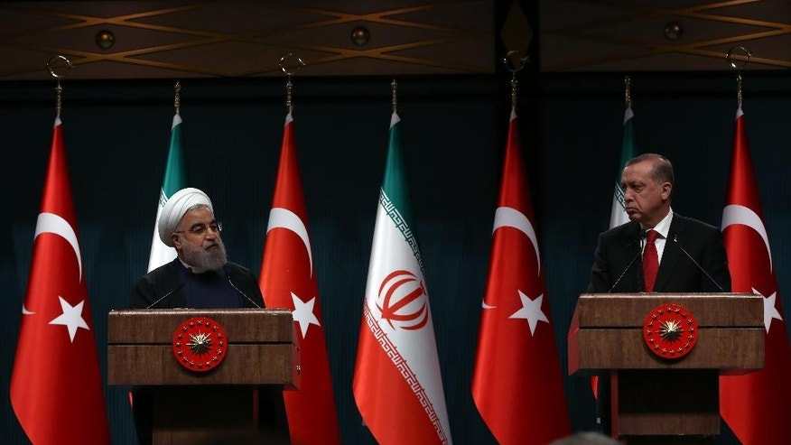 Iran's President Hassan Rouhani, left, and his Turkish counterpart Recep Tayyip Erdogan speak during a joint news conference in Ankara, Turkey, Saturday, April 16, 2016.  Rouhani is in Turkish capital for a one-day official visit. (AP Photo/Burhan Ozbilici)