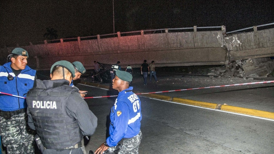 April 16, 2016: Police officers stand next to a collapsed overpass in Guayaquil, Ecuador.