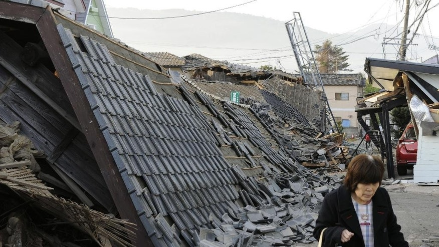 In this Friday, April 15, 2016 photo, a resident walks past collapsed houses in Mashiki, Kumamoto prefecture, southern Japan,  after a magnitude-6.5 earthquake. The powerful earthquake struck Thursday night, knocking down houses and buckling roads. (Ryosuke Uematsu/Kyodo News via AP, File) JAPAN OUT, MANDATORY CREDIT