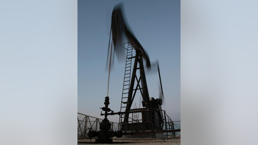 An oil pump works, on Saturday, April 16, 2016, in the desert oil fields of Sakhir, Bahrain. Oil-producing countries are to meet in Qatar on Sunday, April 17, 2016, to discuss a plan to freeze output but their gathering comes as nations like Iran rapidly ramp up their pumping. (AP Photo/Hasan Jamali)