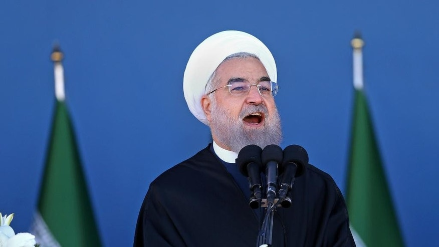 Iran's President Hassan Rouhani speaks at a military parade marking National Army Day in front of the mausoleum of the late revolutionary founder Ayatollah Khomeini, just outside Tehran, Iran, Sunday, April 17, 2016. Rouhani vowed to defend Muslim countries against terrorism and Israel while insisting that its neighbors should not feel threatened. Rouhani praised Iran's role in helping the Syrian and Iraqi governments roll back the Islamic State group. (AP Photo/Ebrahim Noroozi)