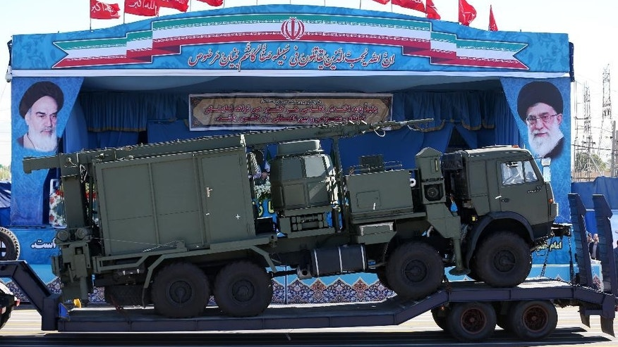 In front of the portraits of supreme leader Ayatollah Ali Khamenei, right, and late revolutionary founder Ayatollah Khomeini, left, a long-range, S-300 missile system is displayed by Iran's army during a parade marking National Army Day at the mausoleum of the late revolutionary founder Ayatollah Khomeini, just outside Tehran, Iran, Sunday, April 17, 2016. Speaking during the parade, Iran's President  Hassan. Rouhani vowed to defend Muslim countries against terrorism and Israel while insisting that its neighbors should not feel threatened. Rouhani praised Iran's role in helping the Syrian and Iraqi governments roll back the Islamic State group. (AP Photo/Ebrahim Noroozi)