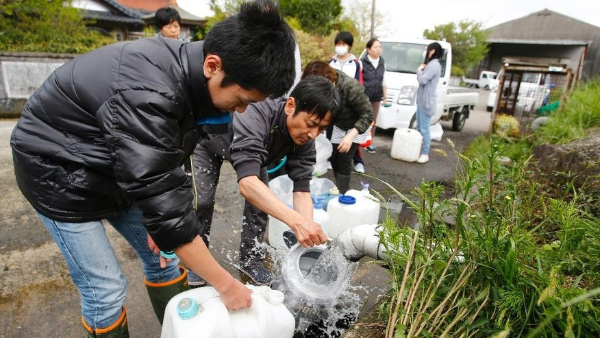 Evacuees collect spring water in plastic containers in Aso, Kumamoto prefecture,  Japan, Sunday, April 17, 2016. Two nights of increasingly terrifying earthquakes flattened houses and triggered major landslides in southern Japan. (AP Photo/Shizuo Kambayashi)