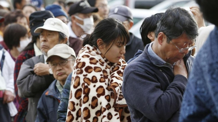 People line up for rations at a shelter in Mashiki, Kumamoto prefecture, Japan Sunday, April 17, 2016. After two nights of earthquakes, flattened houses and triggered major landslides in southern Japan, 91,000 people had evacuated from their homes, according to a Kumamoto prefectural official. (Shohei Miyano/Kyodo News via AP) JAPAN OUT, MANDATORY CREDIT