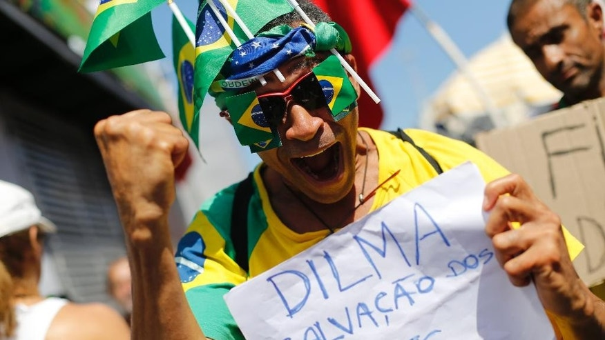 "A man holds a sign that reads in Portuguese ""Dilma is the salvation of the poor"" during a protest against the impeachment of Brazil's President Dilma Rousseff, in Rio de Janeiro, Brazil, Sunday, April 17, 2016. EEmotions have been running high since the impeachment proceedings began in the Chamber of Deputies on Friday, with lawmakers holding raucous, name-calling session. Outside the legislature, waves of pro-and anti-impeachment demonstrators are expected to flood the capital. (AP Photo/Silvia Izquierdo)"