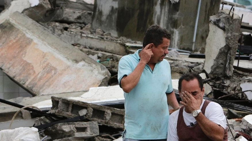 Men cry at as they sit amid the debris of their earthquake demolished house in Pedernales, Ecuador, Sunday, April 17, 2016. The strongest earthquake to hit Ecuador in decades flattened buildings and buckled highways along its Pacific coast, sending the Andean nation into a state of emergency. (AP Photo/Dolores Ochoa)