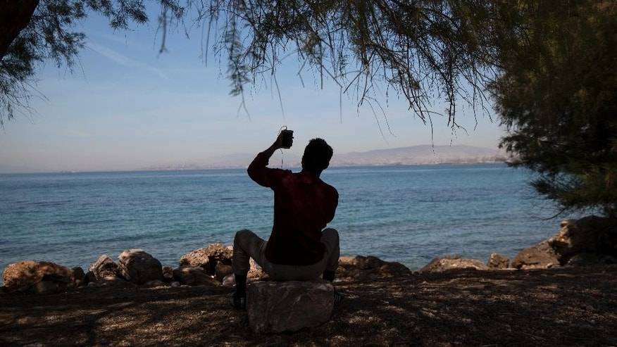 A migrant uses his mobile phone as he sits by the sea near the old international airport which is used as a temporary camp in Athens, on Sunday, April 17, 2016.  Greek authorities, worried about the spread of diseases in makeshift camps, are urging migrants to relocate to organized camps with better living conditions.  (AP Photo/Yorgos Karahalis)