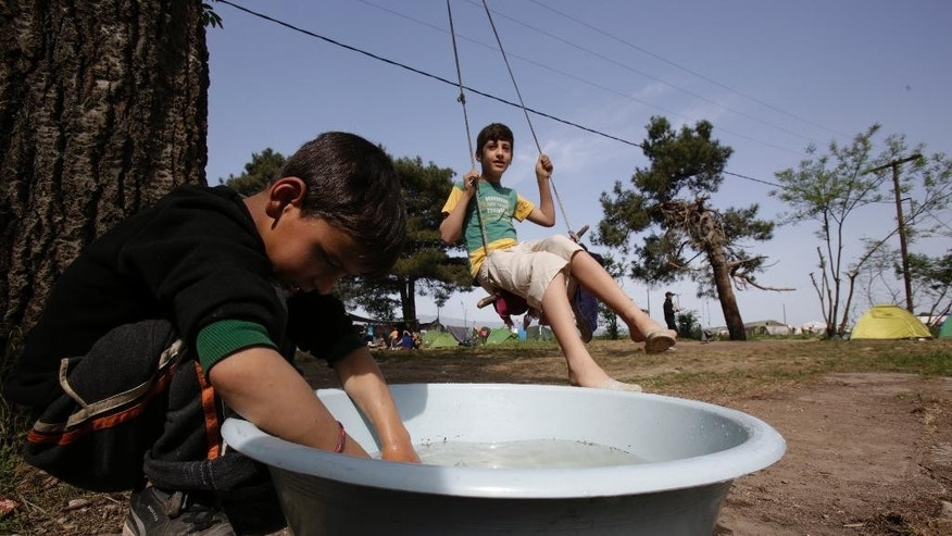 Migrant boy washes dishes while others enjoy a swing chair at the makeshift camp at the northern Greek border point of Idomeni, Greece, Sunday, April 17, 2016.  Some thousands of people have been stuck her for more than a month amid hopes that the border would reopen.(AP Photo/Amel Emric)