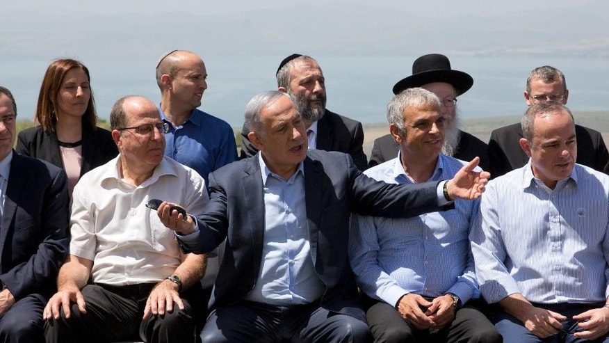 Israeli Prime Minister Benjamin Netanyahu, center, poses with ministers prior to the weekly cabinet meeting in the Israeli controlled Golan Heights, Sunday, April 17, 2016. IIsraeli Prime Minister Benjamin Netanyahu said Sunday his country will never withdraw from the war won Golan Heights and the strategic plateau bordering Syria will forever stay in Israeli hands. (AP Photo/Sebastian Scheiner, Pool)