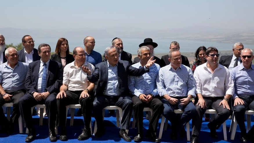 Israeli Prime Minister Benjamin Netanyahu, center, poses with ministers prior to the weekly cabinet meeting in the Israeli controlled Golan Heights, Sunday, April 17, 2016. Israeli Prime Minister Benjamin Netanyahu said Sunday his country will never withdraw from the war won Golan Heights and the strategic plateau bordering Syria will forever stay in Israeli hands. (AP Photo/Sebastian Scheiner, Pool)