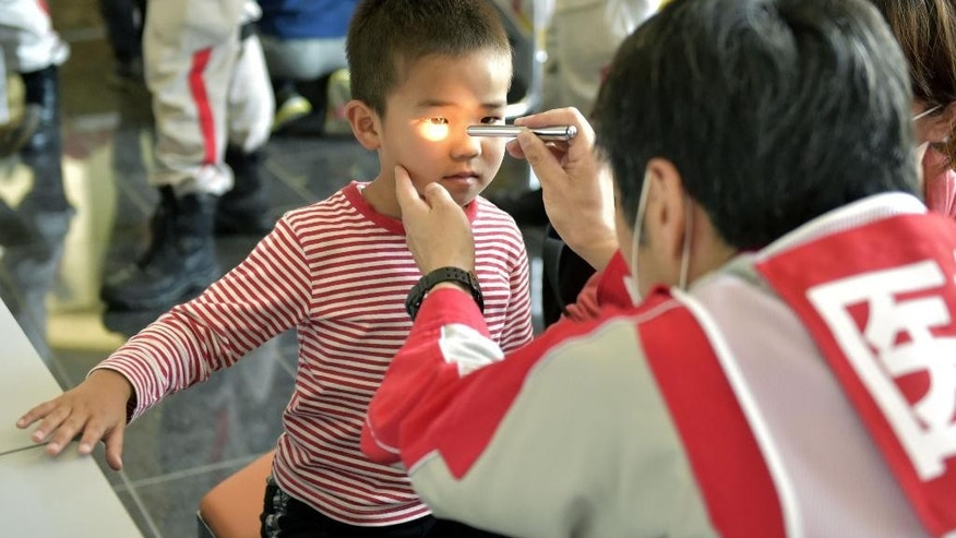 A boy receives medical checkup at a shelter in Mashiki, Kumamoto prefecture, Japan Sunday, April 17, 2016. After two nights of earthquakes, flattened houses and triggered major landslides in southern Japan, 91,000 people had evacuated from their homes, according to a Kumamoto prefectural official.  (Yohei Nishimura/Kyodo News via AP) JAPAN OUT, MANDATORY CREDIT