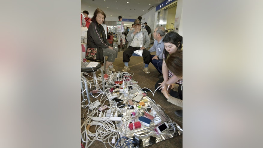 Mobile phones are recharged at a shelter in Mashiki, Kumamoto prefecture, Japan Sunday, April 17, 2016. After two nights of earthquakes, flattened houses and triggered major landslides in southern Japan, 91,000 people had evacuated from their homes, according to a Kumamoto prefectural official.  (Yohei Nishimura/Kyodo News via AP) JAPAN OUT, MANDATORY CREDIT