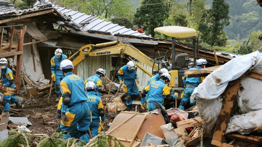 April 17, 2016: Police officers search for missing persons near houses destroyed by landslide in Minamiaso, Kumamoto prefecture.