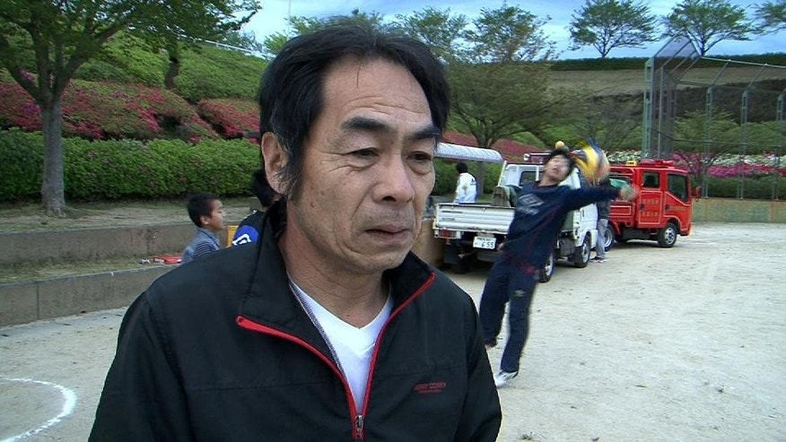 Yoshiaki Tanaka speaks during an interview at a public park in Ozu, Kumamoto prefecture, southern Japan, Saturday, April 16, 2016. The Tanakas joined about 50 other residents of the southern Japanese town of Ozu who were planning to sleep in their cars at a public park Saturday after two nights of increasingly terrifying earthquakes that flattened houses and triggered major landslides.(AP Photo/Richard Colombo)
