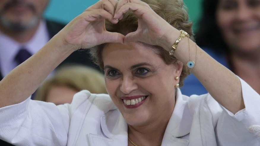 April 12, 2016: Brazil's President Dilma Rousseff makes a heart sign during a ceremony with teachers and students at Planalto presidential palace in Brasilia.