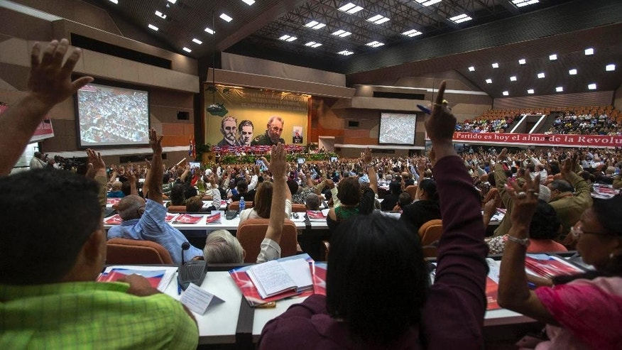 Communist Party delegates raise their hands during a vote in a session of the 7th Congress of the Cuban Communist Party of in Havana, Cuba, Monday, April 18, 2016. (Ismael Francisco / Cubadebate via AP)