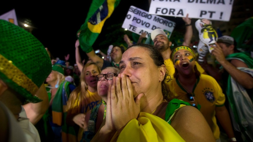 Anti-government demonstrators celebrate after the lower house of Congress voted to impeach Brazil's President Dilma Rousseff.