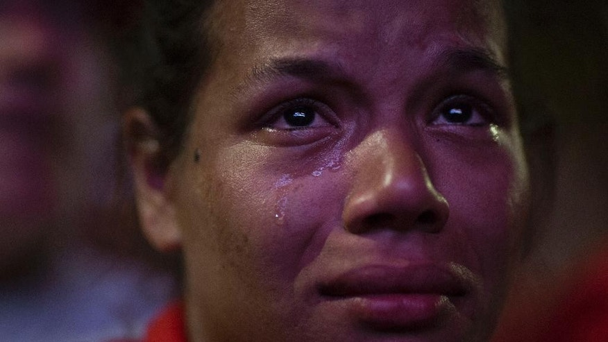 A pro-government demonstrator cries as she watches the vote count broadcast live on a screen, as lawmakers decide on whether or not to impeach Brazil's President Dilma Rousseff, in Brasilia, Brazil, Sunday, April 17, 2016. The vote will determine whether the impeachment proceeds to the Senate. Rousseff is accused of violating Brazil's fiscal laws to shore up public support amid a flagging economy. (AP Photo/Felipe Dana)