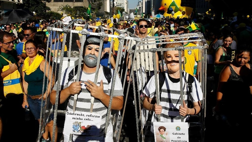 Demonstrators wearing costumes of Brazil's former President Luiz Inacio Lula da Silva, left, and current President Dilma Rousseff march inside mock jail cells, during a protest demanding Rousseff's impeachment in Sao Paulo, Brazil, Sunday, April 17, 2016. Sunday's vote in the lower house will determine whether the impeachment proceeds to the Senate. Rousseff is accused of violating Brazil's fiscal laws to shore up public support amid a flagging economy. (AP Photo/Andre Penner)