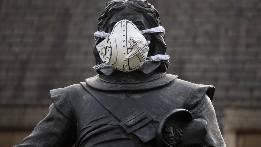 A custom-made clean air mask is seen placed on the face of the Oliver Cromwell statue outside the Houses of Parliament by Greenpeace activists to protest against air pollution quality in London and cities across the UK, Monday, April 18, 2016.  (AP Photo/Matt Dunham)