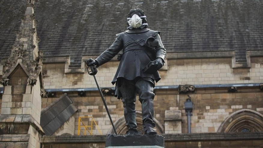 A clean air mask is seen placed on the face of the Oliver Cromwell statue outside the Houses of Parliament by Greenpeace activists to protest against air pollution quality in London and cities across the UK, Monday, April 18, 2016.  (AP Photo/Matt Dunham)