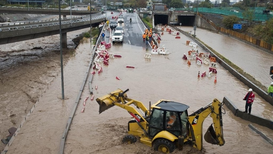 Machinery works in the middle of a flooded street in Santiago, Chile, Sunday, April 17, 2016. Authorities say the Rio Mapocho flooded several districts of the city and landslides killed at least one person. (AP Photo/Esteban Felix)