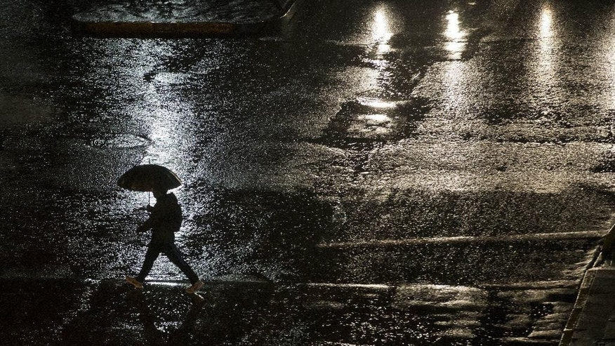 A man walks under the rain in Santiago, Chile, Saturday, April 16, 2016. Authorities say the Rio Mapocho flooded several districts of the city and landslides killed at least one person. (AP Photo/Esteban Felix)