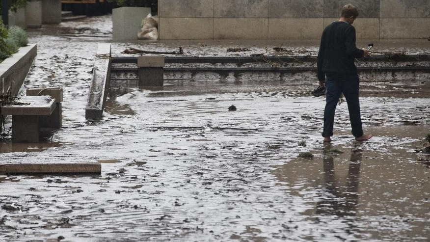 A man walks in the middle of the mud covered street after a flood in Santiago, Chile, Sunday, April 17, 2016. Authorities say the Rio Mapocho flooded several districts of the city and landslides killed at least one person. (AP Photo/Esteban Felix)