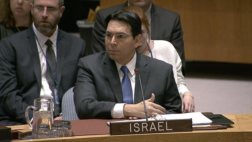 In this image made from a video provided by UNTV, Israel's Ambassador Danny Danon, center, and Palestinian envoy Riyad Mansour, not pictured, speak to one another at an United Nations Security Council meeting Monday, April 18, 2016, at United Nations headquarters. (UNTV via AP) MANDATORY CREDIT