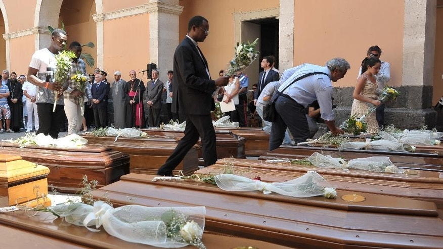 FILE - In this Tuesday, July 7, 2015 file photo, people lay flowers on coffins during the funeral of 13 migrants who were among up to 800 people who died in a shipwreck in April in Catania, Sicily, Italy. Exactly one year after a fishing boat crowded with smuggled migrants capsized, sinking to the Mediterranean Sea floor with some 800 people trapped inside, Italy is launching efforts to raise up the ship and bring it to a Sicilian port. Italian naval ships were setting sail Monday evening from Sicily for the shipwreck site. (AP Photo/Carmelo Imbesi, File)