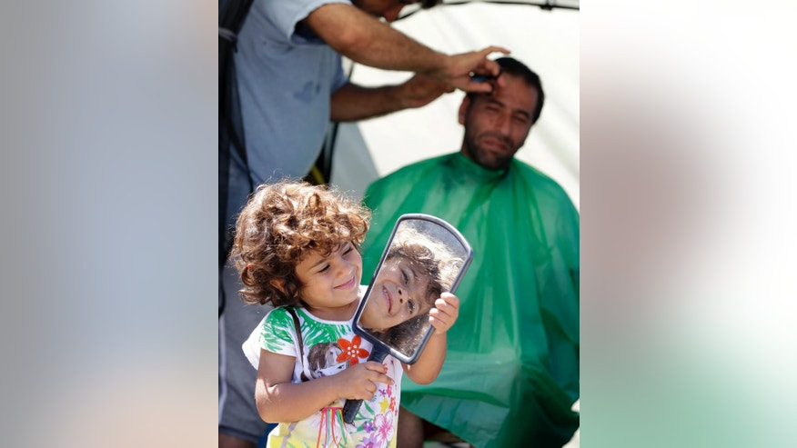 A girl plays with a mirror as a Syrian refugee gets a hair cut inside a tent at the Athens port of Piraeus, on Monday, April 18, 2016. Hundreds of refugees and migrants continue to move at government-built shelters but more than 3,500 people remain at Piraeus. The Greek authorities are trying to evacuate the biggest port of the country, before Orthodox Easter on May 1, from refugees and migrants who are  using tents and the terminal passenger buildings to stay. (AP Photo/Thanassis Stavrakis)