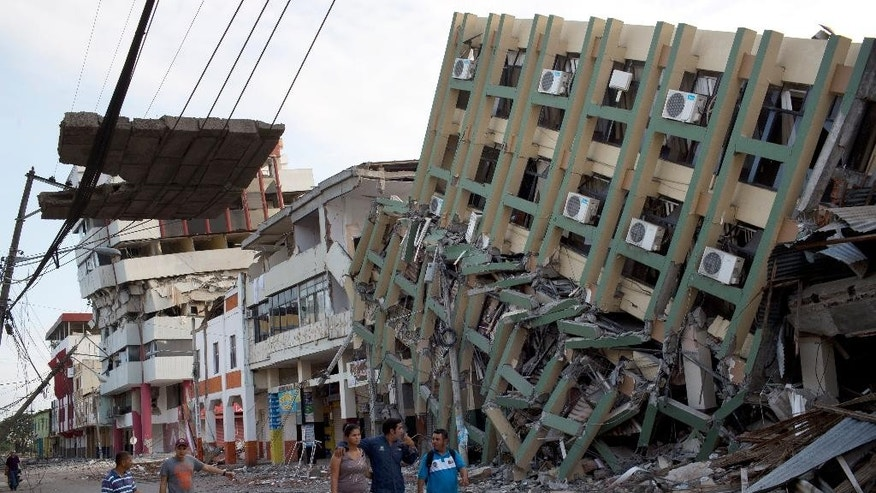 Residents walk past a row of collapsed buildings felled by the 7.8-magnitude earthquake, in Portoviejo, Ecuador, Monday, April 18, 2016. The Saturday night quake left a trail of ruin along Ecuadorís normally placid Pacific Ocean coast. At least 350 people died and thousands are homeless. President Rafael Correa said early Monday that the death toll would ìsurely rise, and in a considerable way.î (AP Photo/Rodrigo Abd)