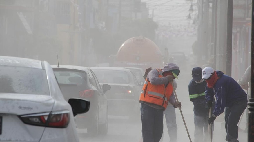 Workers sweep ash off the streets of San Andres Cholla, Mexico, Monday April 18, 2016, after the Popocatepetl volcano erupted overnight, spewing ash on nearby towns. Officials there are urging to people to wear masks to avoid inhaling the fine grit that has covered houses and cars. (AP Photo/Pablo Spencer)