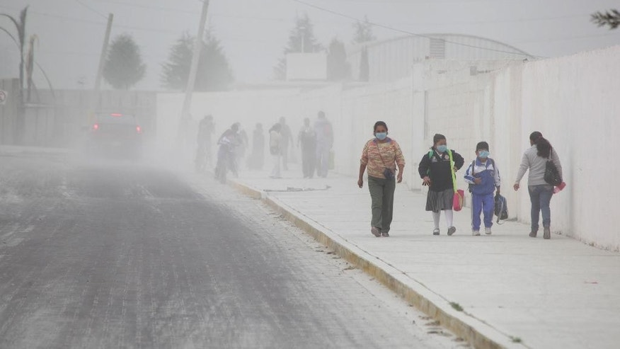 People walk on the ash-covered streets of San Andres Cholla, Mexico, Monday April 18, 2016, after the Popocatepetl volcano erupted overnight, spewing ash on nearby towns. Officials there are urging to people to wear masks to avoid inhaling the fine grit that has covered houses and cars. (AP Photo/Pablo Spencer)