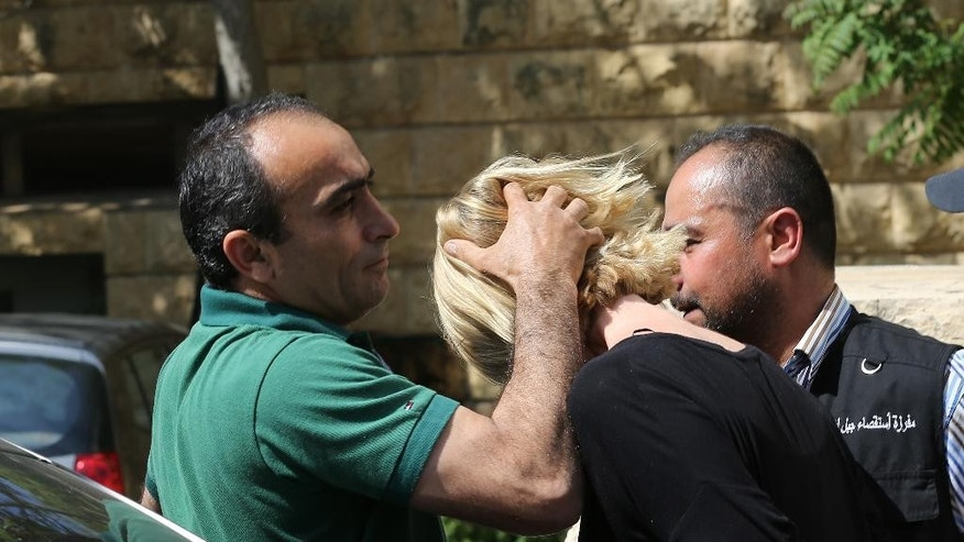 A Lebanese plainclothes policeman prevents Australian TV presenter Tara Brown from looking towards journalist as she was taken from a Lebanese courthouse where she was questioned by an investigative judge over suspicion of taking part in an abduction attempt of two Lebanese-Australian children, in Baabda, east of Beirut, Lebanon, Monday April, 18, 2016. (AP Photo/Hussein Malla)