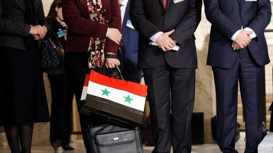 A member of the Syrian government holds a bag with the colors of the Syrian flag during a press conference of the Syrian chief negotiator Bashar al-Jaafari, Ambassador of the Permanent Representative Mission of Syria to the UN after a round of negotiations between the Syrian government and UN Special Envoy for Syria Staffan de Mistura in Geneva, Switzerland, Monday, April 18, 2016. (Salvatore Di Nolfi/Keystone via AP)