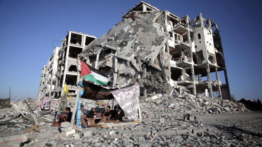 FILE - In this Aug. 11, 2014 photo, Palestinian Ziad Rizk sits with others in a shelter made of a blanket stretched over four boles next to one of the destroyed Nada Towers, where he lost his apartment and clothes shop, in the town of Beit Lahiya, northern Gaza Strip. A new report released Monday, April 18, 2016, by the World Bank shows that Qatar, the United Arab Emirates and other Arab donors have delivered only a small fraction of aid that was promised to help the devastated seaside enclave after Israel's war against Gaza militants in 2014. (AP Photo/Khalil Hamra, File)